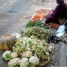 Une femme assis au sol ve,ds ses legumes dans une rue de la médina de Marrakech